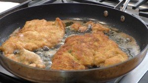 Chicken Parmesan sizzling in pan